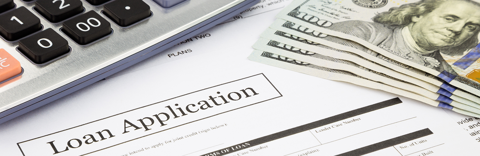 Stock photo of loan application with calculator and cash